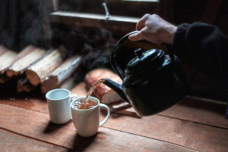 Person laver te i gammel hytte
