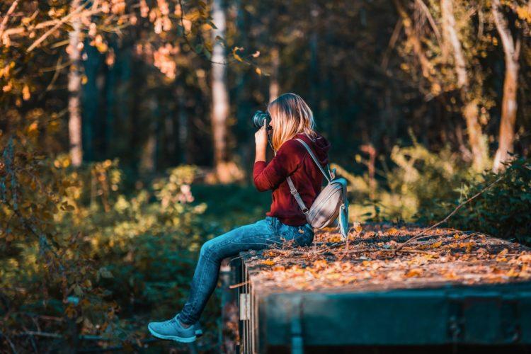 Pige tager billeder med kamera i naturen