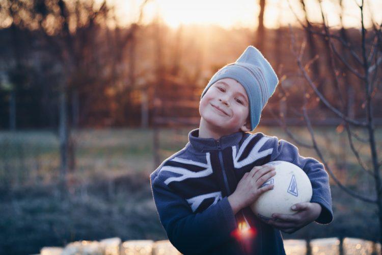 Dreng er udenfor med bold under armen