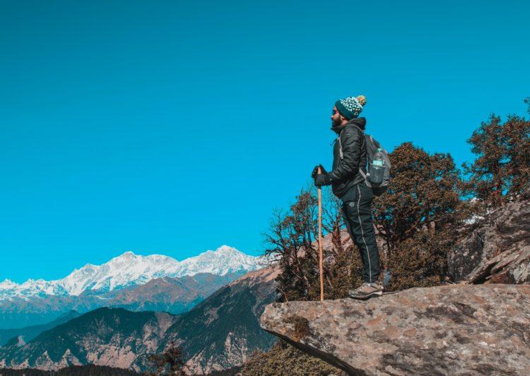 Mand har outdoor udstyr på i bjergene