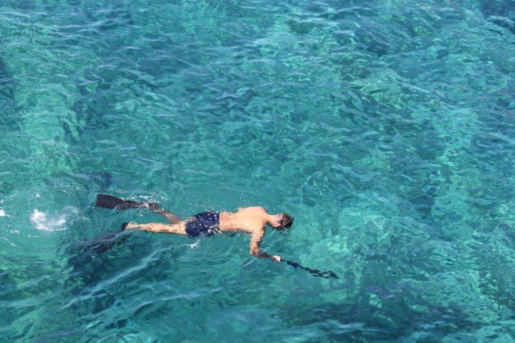 mand svømmer rundt med svømmefødder